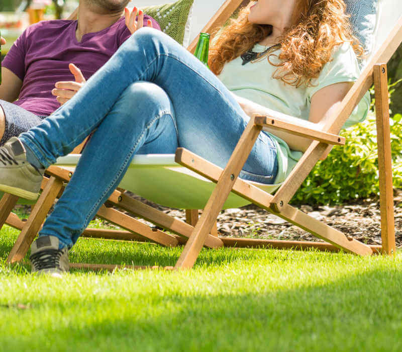 Man and Woman relaxing in chairs in backyard
