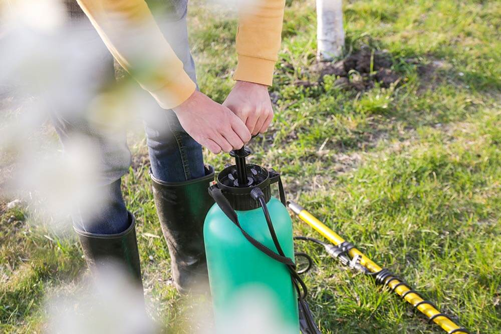 Tips & Tricks to prepare for the season, hands pumping green sprayer outside