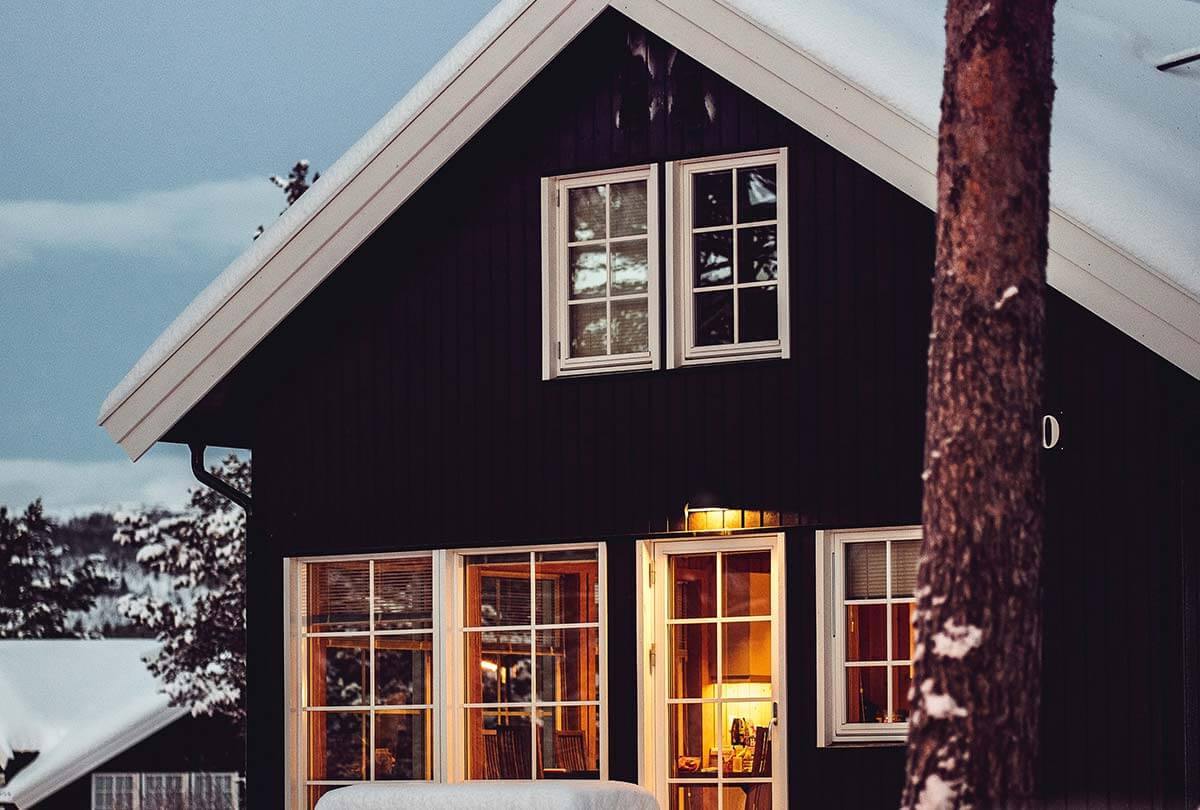 Pest-proofing a home in the new year – black and white house with snow, tree in front, light inside seen through windows and door