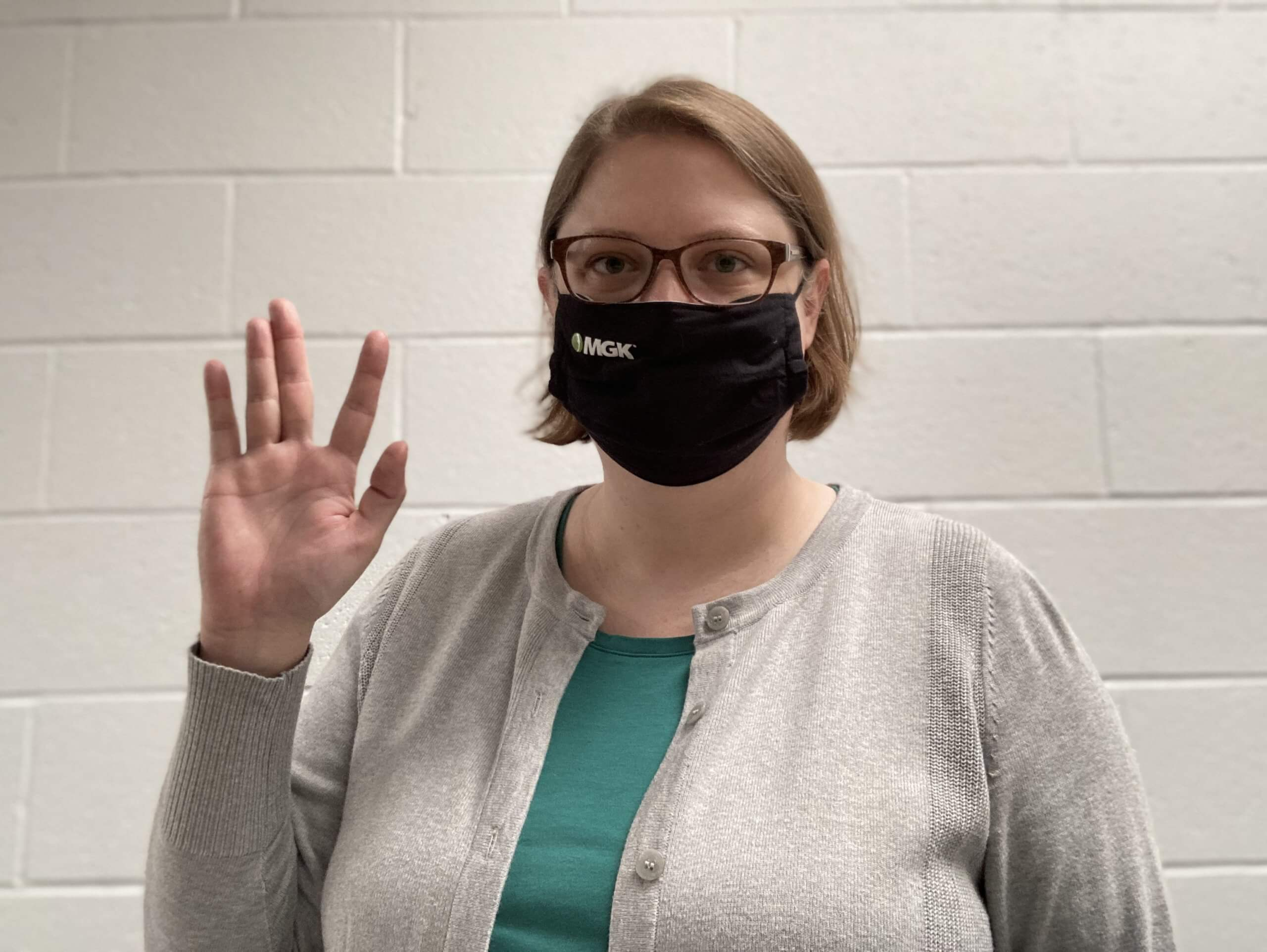 Abby Smith - International Women's Day pose with hand up, wearing MGK branded mask